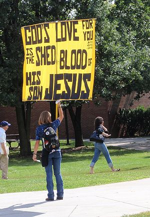 English: Young woman carries large yellow sign...