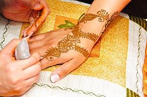 English: Applying Mehndi in hand