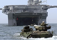 color photo of swimming AAVs approaching the well deck of an amphibious assault ship