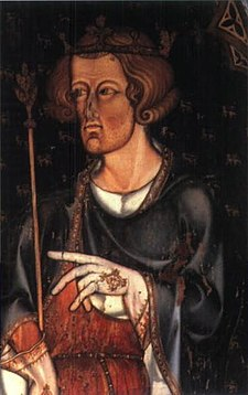 A man in half figure with short, curly hair and a hint of beard is facing left. He wears a coronet and holds a sceptre in his right hand. He has a blue robe over a red tunic, and his hands are covered by white, embroidered gloves. His left hand seems to be pointing left, to something outside the picture.