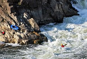 A whitewater kayaker, whose boat is hidden in ...
