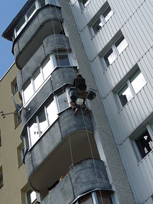 English: Painter preparing balcony surface for...