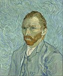 A mid to late 30s intense man with red beard gazing to the left wearing a green coat.