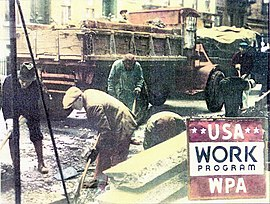 """Workers digging in a street with their shovels; a red truck is seen in the background and """"USA Work Program WPA"""" is spelled out in the lower right."""