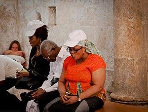 People praying at the Cenacle in Jerusalem.