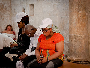 People praying at the Cenacle in Jerusalem.