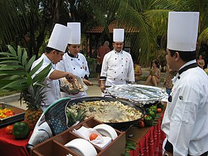 English: Chefs preparing a seafood paella in P...