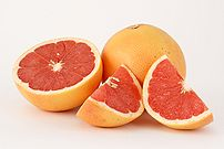 This photograph shows two pink grapefruits (Citrus ×paradisi), one of the two cut in pieces.