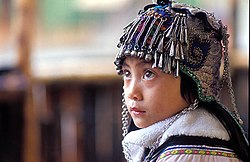 An ethnic Hani girl with a typical Hani headgear for children. Near Yuanyang, Yunnan Province, China.