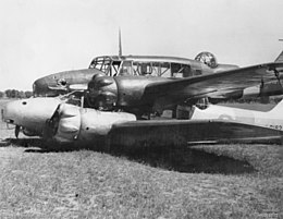 Side view of two military monoplanes lying wheels up on a field, one atop the other