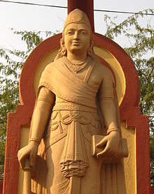 Statue of a standing young man in red stone.