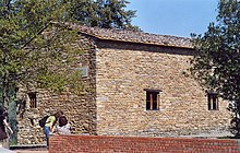 Photo of a building of rough stone with small windows, surrounded by olive trees.