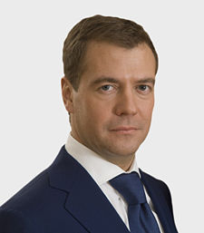 A portrait shot of a serious looking middle-aged male looking straight ahead. He has short brown hair, and is wearing a blue blazer with a blue tie over a white collared shirt.