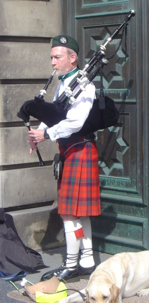 A bagpiper in national dress with his golden Labrador lying at his feet.