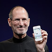 Jobs smiling and holding an iPhone
