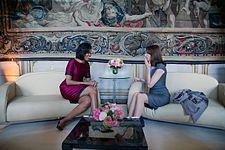 Michelle Obama en Carla Bruni Delen Een lach zittend op aangrenzende Banken.