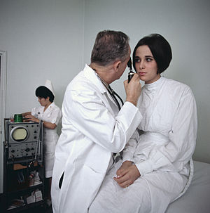 English: A doctor examines a female patient.