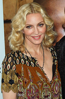 Upper body of a middle-aged blond woman. Her hair is parted in the middle and falls in waves to her shoulder. She is wearing a loose dress with black and brown prints on it. A locket is hung around her neck, coming up to her breasts. She is looking to the right and is smiling.