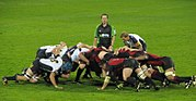 Two opposing formations of eight men, in white and black to the left, red and black to the right, push against each other in a crouched position; behind them stands another player and the referee.
