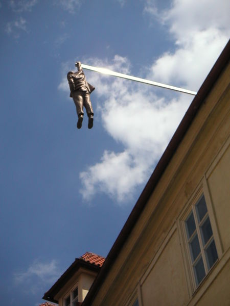Statue of Sigmund Freud hanging by his arm, above a storefront in Prague