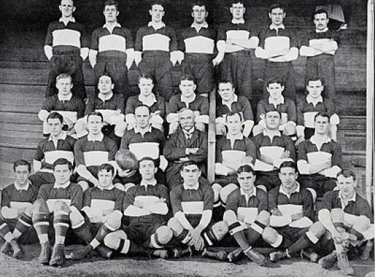 A group of rugby union players posing in several rows while wearing their uniforms