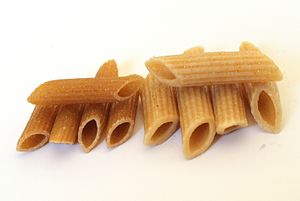 Whole wheat penne pasta, cooked (right) and un...
