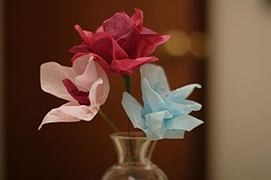 Delicate paper flowers in a vase. One pink, on...