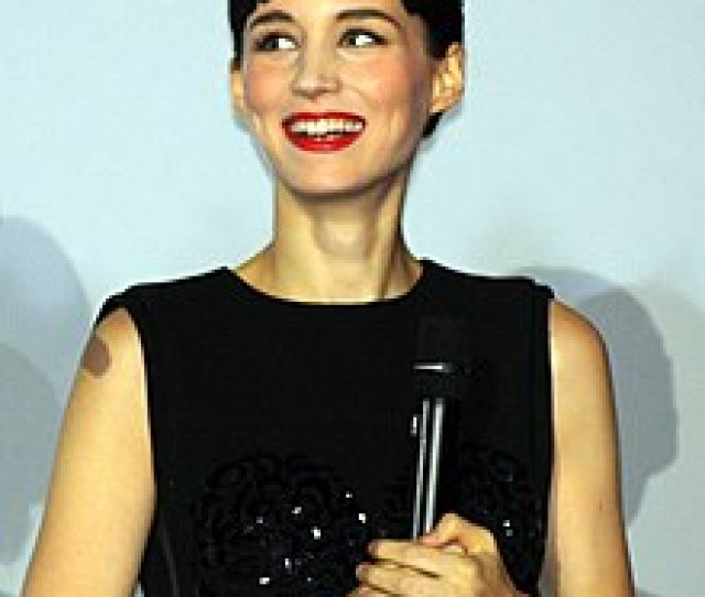 A Smiling Woman With Short Hair Wears A Black Dress