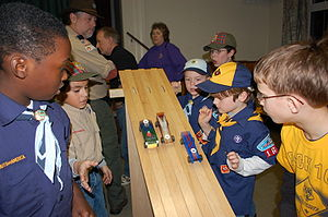 Cub Scouts watch three pinewood derby cars sta...