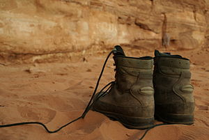 A pair of Lowa hiking boots on red desert sand...