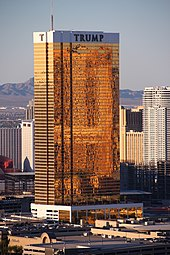 A tall rectangular-shaped tower in Las Vegas with exterior windows reflecting a golden hue. It is a sunny day and the building is higher than many of the surrounding buildings, also towers. There are mountains in the background.