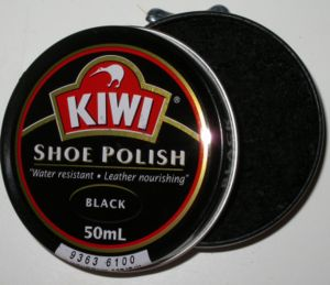 An open can of shoe polish with a side-mounted...