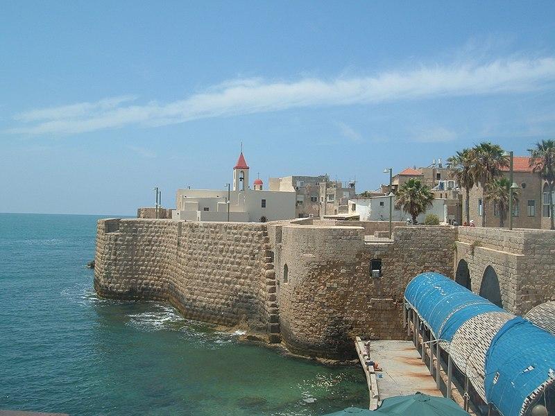 en 638 par les arabes. Cette domination s'achève avec Baudouin Ier, le 26 mai 1104, lorsque la ville tombe aux mains des croisés. Reprise par le sultan Saladin, le 9 juillet 1187, elle est reconquise par les rois Philippe-Auguste et Richard Cœur-de-Lion durant la troisième croisade en juillet 1191. Elle devient au xiiie siècle la capitale du Royaume de Jérusalem et le principal port de Terre sainte. Au moins dès le xiie siècle, des hommes s'inspirant du prophète Élie vivent en ermites dans les grottes du mont Carmel. Albert Avogadro, patriarche latin de Jérusalem, leur donne vers 1209 une règle de vie centrée sur la prière. L'appellation officielle de ce très ancien institut est celle d'Ordre de Notre Dame du Mont-Carmel, mais on les appelle habituellement en français les Grands Carmes.  L'installation de l'ordre des Hospitaliers de Saint-Jean de Jérusalem et la fondation de l'Hôpital apportent à la ville un nouveau nom, celui de Saint-Jean-d'Acre. Jusqu'en 1291, la ville sera un grand centre intellectuel, non seulement chrétien mais aussi juif. En effet, de nombreux Juifs, souffrant de persécutions en Occident, se rendent en Terre sainte. Le rabbin Yehiel de Paris y fonde une yeshiva qui sera connue au-delà de la Terre Sainte. Nahmanide, grand kabbaliste d'Espagne le remplacera. En 1291, la ville est prise par les mamelouks. Cette date marque la fin du royaume latin de Jérusalem et de la présence occidentale en Terre Sainte.  Durant les croisades, la vieille ville d'Acre était divisée en quartiers contrôlés par des marchands venus de tout le pourtour méditerranéen, notamment vénitiens, pisans, gênois, français et germaniques.