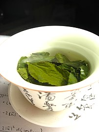 {{en}}Green tea leaves steeping in an uncovere...