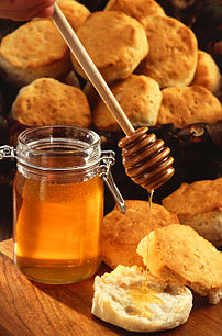 A jar of honey, shown with a wooden honey dipp...