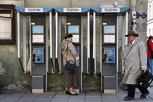 English: Lady talking to a pay phone in Tallin...