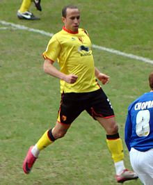 A young man, wearing a yellow top, standing on a grass field.