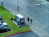 Riders waiting at a U.S. bus stop with a shelter.