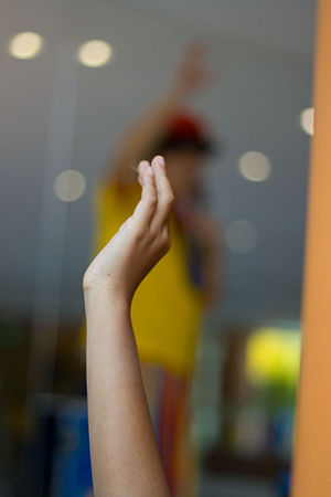 English: A student raising a hand to ask a que...