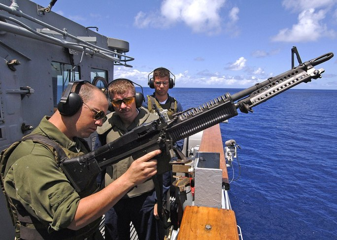 US Navy 060417-N-1045B-005 Seaman Thomas J. Tafoya, left, receives instruction on firing an M-60 machine gun from Chief Gunner's Mate Louis Johnson during a live fire exercise aboard the Ticonderoga-class guided missile cruiser