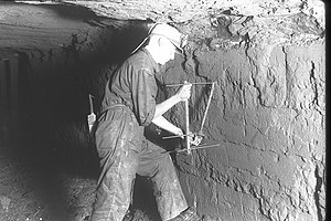 A miner measures mine minerals