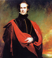 A three-quarter length portrait of a standing man wearing a black cloak with gold buttons, and a red stole with tassels