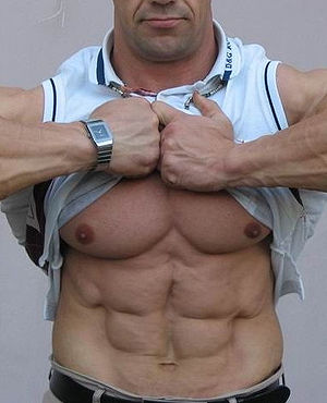 A man lifts his shirt up to expose his well-de...