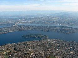 Aerial view of Mercer Island, the large island surrounded by Lake Washington. The smaller forested peninsula jutting into the lake from the Seattle mainland is Seward Park.