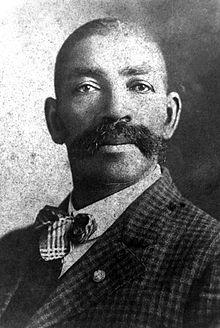 Foto de Bass Reeves, com seu bigode enorme, olhando seriamente. Terno xadrez e gravata dos anos 1900. Ele tem os cabelos bem curtos, raspados. E uma expressão altiva.