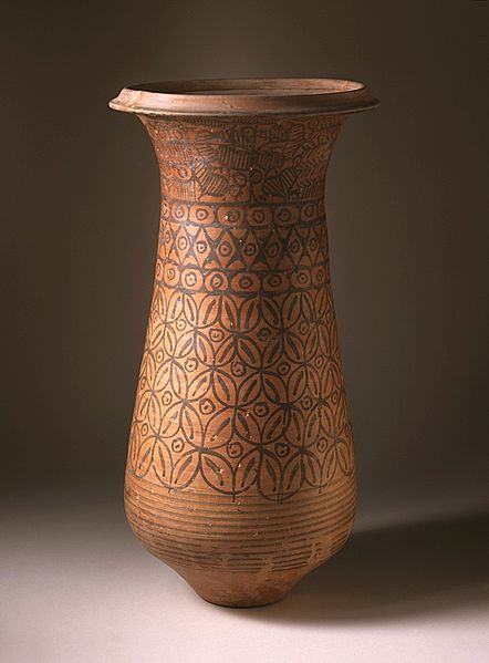 A large, glazed, red-blown pot with geometric flower patterns on it.