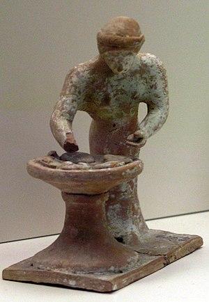 Figurine de femme en train de pétrir de la pât...