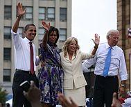 Barack en Michelle Obama en een vrouw nl Een man op Een buitenpodium.  De eerste three Glimlach en golf.  De mannen Dragen pak broek, witte Overhemden met de mouwen opgerold, en Stropdassen.  Michelle is in Een colorful afdruk jurk en de andere vrouw is in Een creme pak.
