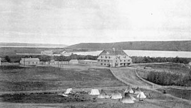 Exterior view of Qu'Appelle Indian Industrial School in Lebret, District of Assiniboia, c. 1885. Surrounding land and tents are visible in the foreground.