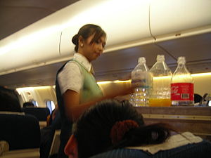 PBair female flight attendant at work on board...